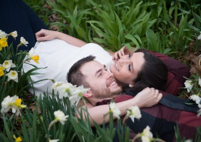couple lying in a field of daffodils engagment photography