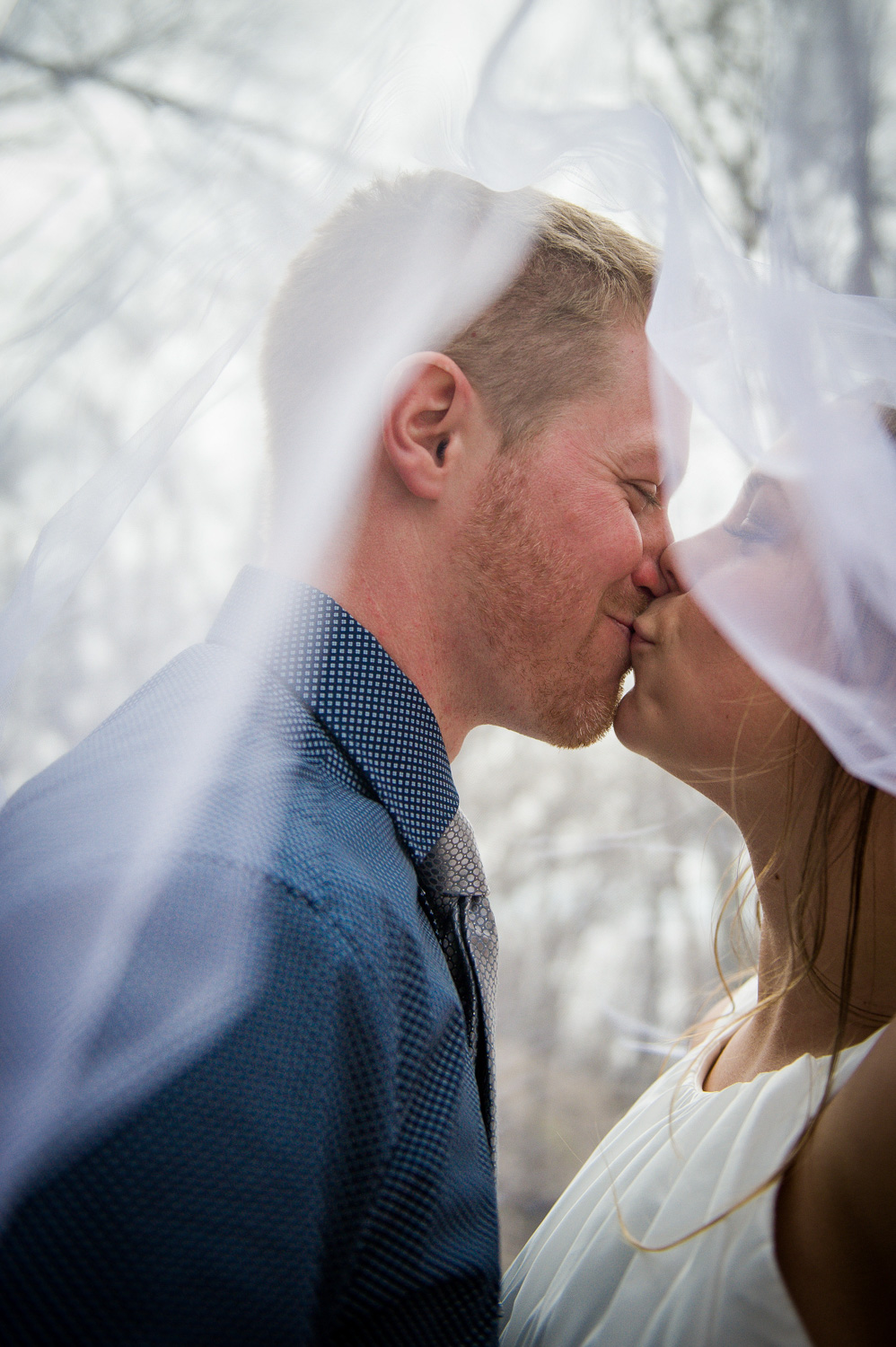 bride and groom kissing under bride's veil