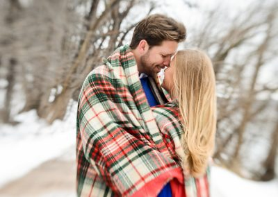 Winter engagement photography session couple wrapped in plaid blanket