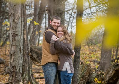 Couple hugging in autumn forest engagment photography session