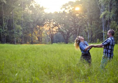 engagment photography session couple spinning in a green field