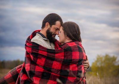 engagement photography session couple wrapped in red and black plaid blanket