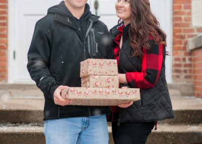 Snowy engagement photography couple holding gifts
